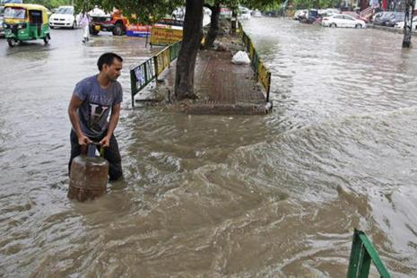 A man carries a gas cylinder through a flooded street during a rainstorm in New Delhi on Saturday. Photo: AP