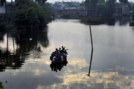 People on boat move during flooded river in Didarganj area in Patna on Saturday. Photo: PTI
