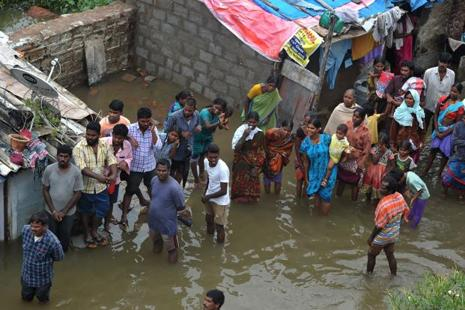 Residents stand in floodwater outside their homes following heavy rain in Alwal on the outskirts of Hyderabad on 23 September. Photo: AFP