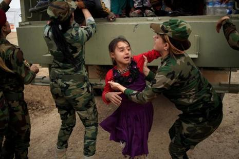 Kurdish Female Peshmerga soldiers helps a newly internally displaced girl upon her arrival at Al Khazar Camp near Hassan Sham, east Of Mosul. Photo:Reuters