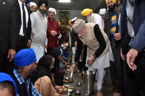 Prime Minister Narendra Modi serves langar during his visit at Golden Temple in Amritsar on Saturday. Photo: PTI