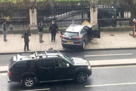 People stand near a crashed car on Bridge Street near the Houses of Parliament in London, which was under terrorist attack, on Wednesday. Photo: AP