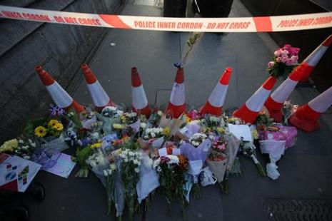 A pile of floral tributes to the victims of the 22 March terror attack in Westminster at the north end of Westminster Bridge by the Houses of Parliament in central London on 23 March. Photo: AFP