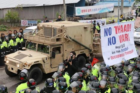Protesters and police stand by as trailers carrying US THAAD missile defence equipment enter a deployment site in Seongju, on Wednesday. Photo: AFP
