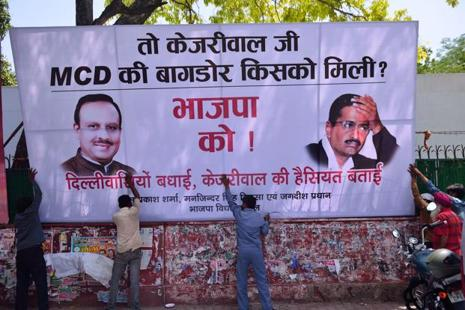 Workers put up a hoarding outside Delhi BJP headquarters in New Delhi on Wednesday. The party dedicated its landslide win in MCD elections 2017 over AAP and Congress to CRPF jawans killed in the Sukma Naxal attack. Photo: Pradeep Gaur/Mint