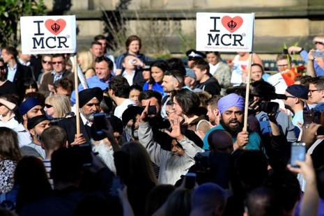 Sikhs wave placards before a vigil for the victims of Manchester Arena attack, in Manchester on Tuesday. Photo: Reuters