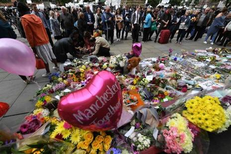 Balloons and flowers are seen in Albert Square in Manchester on Wednesday, placed in tribute to the victims of the 22 May Manchester Arena attack. Photo: Chris J. Ratcliffe/AFP