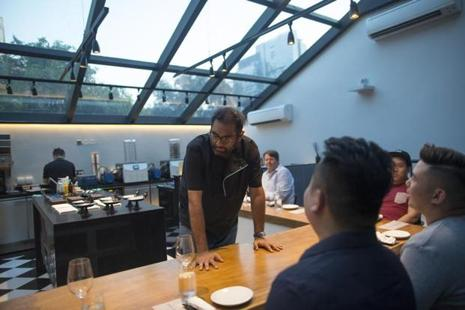 Chef Gaggan Anand (C) interacts with customers sitting at the chef's table inside the research and development kitchen at Gaggan restaurant in Bangkok, Thailand, on Friday. Photo: Brent Lewin/Bloomberg