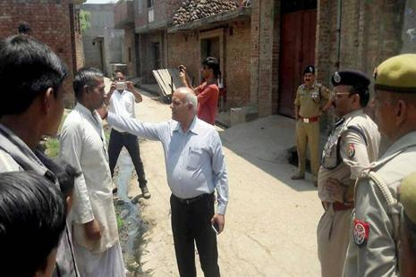 UP home secretary Mani Prasad Mishra talks to the persons affected by the violence in Saharanpur, in Shabbirpur on Wednesday. Photo: PTI