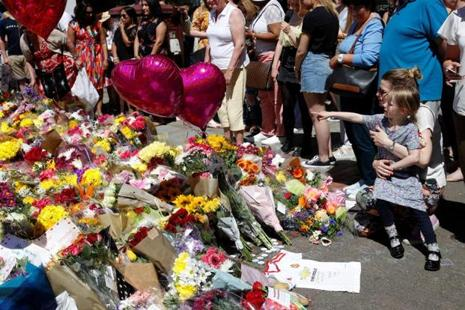 People look at tributes to the victims of the Manchester Arena attack, in central Manchester, Britain, on Friday. Photo: Phil Noble/Reuters