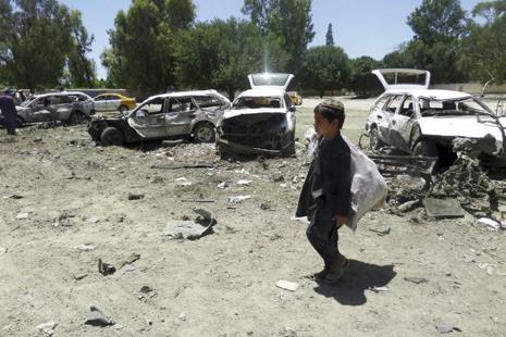 A boy walks past damaged vehicles at the site of a suicide attack in eastern Khost province in Afghanistan. If the US exits Afghanistan without a settlement in place, the ensuing instability might boomerang on Pakistan. Photo: AP