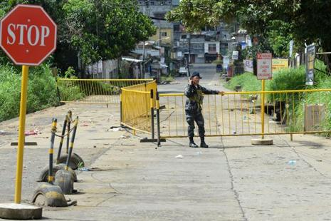 A member of the police special forces stands guard at a deserted intersection in Marawi on the southern island of Mindanao on Sunday. Photo: AFP