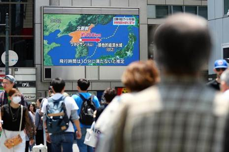 People walk near a screen which reports North Korea's missile launch on Monday. North Korea fired a short-range ballistic missile that landed in Japan's maritime economic zone. Photo: AP
