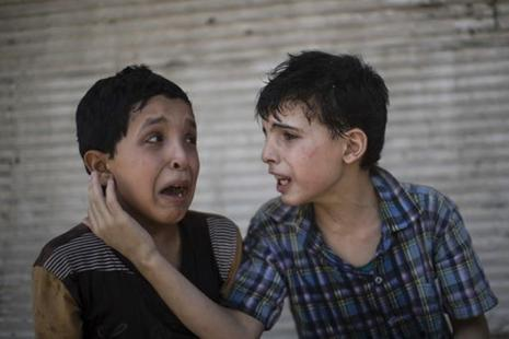 Cousins Zeid Ali (12) and Hodayfa Ali (11) comfort each other after their house collapsed during fighting between Iraqi forces and IS militants in Mosul, Iraq, on Saturday. Photo: Felipe Dana/AP