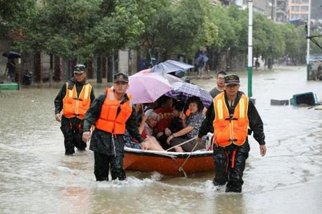 Rescuers evacuate people after heavy rainfall flooded streets in Xiushui County, Jiangxi province, China on Saturday. Photo: Reuters