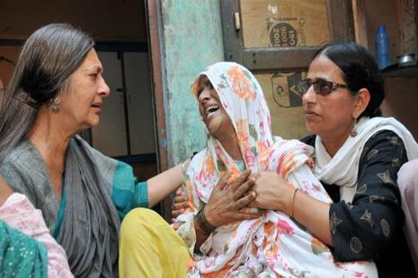 File photo of Junaid's mother (centre). Junaid was stabbed when he along with his brothers was returning home to Khandawli village in Ballabgarh on 22 June. Photo: PTI