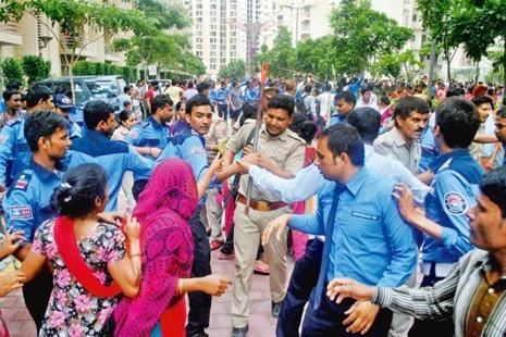 Private security personnel and police trying to restrain maids on the Mahagun Moderne premises in Noida. Photo: PTI