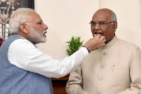Prime Minister Narendra Modi offers sweets to Ram Nath Kovind as he congratulates him on being elected as the 14th President of India, in New Delhi on Thursday. Photo: PTI