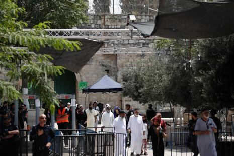 Muslim tourists walking past Israeli security measures as they exit through Lions' Gate, a main entrance to Al-Aqsa mosque compound in Jerusalem. Photo: AFP