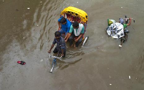 A rickshaw puller wades through a water-logged street following heavy rains in Allahabad on Tuesday. Photo: AP