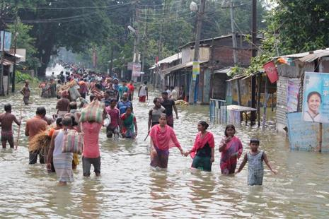 Residents wade through flood waters in Balurghat in West Bengal on 17 August. Photo: AFP