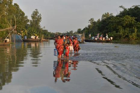 Villagers wade through a flooded state highway at Chachol village in Malda district of West Bengal. Photo: AFP