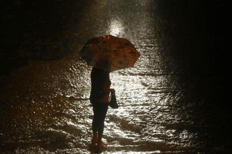 A woman waits for transport in the rain in Mumbai on Tuesday. Photo: AP