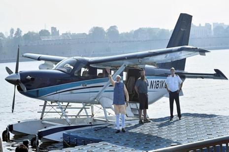 Prime Minister Narendra Modi waves to the crowd as he boards a seaplane on the Sabarmati river front in Ahmedabad on Tuesday. Photo: PTI