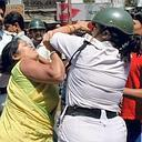 A protester and a policewoman in a scuffle