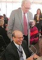 Guiding hand: Warren Buffett looks over the shoulder of Ajit Jain, head of the reinsurance unit with Berkshire Hathaway Inc., while he plays bridge.