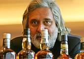 Cheers: UB Group chairman Vijay Mallya examines bottles of whisky maker Whyte and Mackay.
