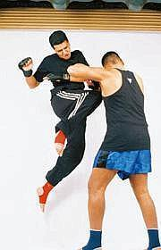 High kicks: Pastor Daniel Isaac (in black track pants) at practice with one of his kickboxer trainees at his Nashik gymnasium.