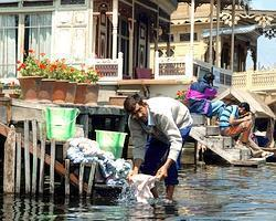 A man washes clothes in the waters of the Dal Lake. The Lake, famed for its ornately-carved cedar houseboats, is the centrepiece of Srinagar's tourist trade.