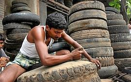 Closer to hub: A worker shreds rubber tyres for scrap at a workshop in Mumbai. With India and China commanding a bigger share in the global rubber trade, the London-based group has decided to shift cl