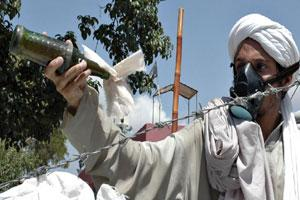 A masked student of Lal Masjid, or Red Mosque, shakes a 'petrol bomb' in Islamabad on 3 July.