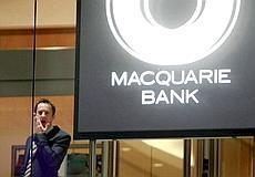 A man stands next to a Macquarie Bank logo in Sydney on August 1. Australia's Macquarie Bank warned on Wednesday that retail investors in two debt funds face losses of up to 25% as fallout from the gl