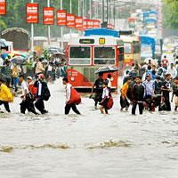 In God's Hands: People move through a flooded road after heavy rains in Mumbai. India's monsoon rains are reviving after a weak phase since mid-July and will gather momentum, the Met department has sa