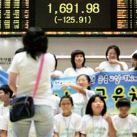Big drop: Elementary school students take a picture at the Korea Stock Exchange Market in Seoul. Korea's Kospi stock index fell 6.9%—or 125.91—to close at 1,691.98, its biggest decline in more than fi