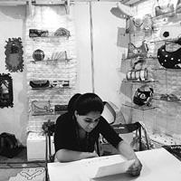 A volunteer in a stall of eco-chic handbags in a New Delhi exhibition on 6 September