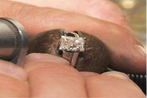 Diamonds aren't always forever: A jeweller uses a loupe to look at a 1.5 carat diamond in his workshop. Synthetic or chemically treated diamonds, which are 30% cheaper than natural diamonds, are gradu