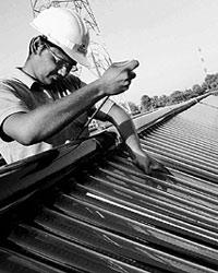 An engineer does maintenance work on tube solar collectors at Mamata Energy Ltd in Gujarat