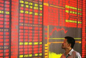 Market review: A man checks information at a stock exchange board in China. The nation's booming market for stocks has made the shares of Chinese brokerages, including Citic Securities, more expensive