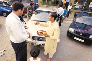 Enticing offers:  Buyers outside a car showroom in New Delhi.
