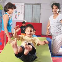 Fun gym: Ashar (left) puts a child through the paces