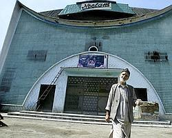 A Kashmiri Muslim leaves after selling cold drinks at the Neelam cinema, the only functional cinema hall in Srinagar