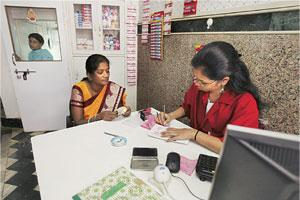 Breaking away: A sex worker deposits money into her account at the Sangini Women's Cooperative Bank in Mumbai. The small bank, set up in the Kamathipura area, is the initiative of the sex workers, aim