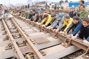 Building spree: A file photo of labourers laying down new tracks for a high-speed passenger rail line connecting Nanjing and Hefei at a railway station in Hefei, Anhui province. China and India are bo