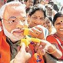 Good times: Supporters in Bangalore offer sweets to a party worker wearing a Narendra Modi mask during a rally to celebrate the party's Gujarat win. The Congress had pinned its hopes on a win in the s