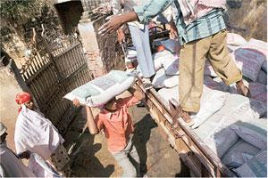 Getting pricier: A file photo of labourers unloading cement in Gurgaon. Coal constitutes around 12% of the total operating cost of the sector.