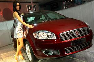 Complementing looks: A model poses with the newly unveiled Fiat Linea ahead of the 9th Auto Expo in New Delhi on Wednesday. Car makers are increasingly hiring modelling agencies to spice up the show.